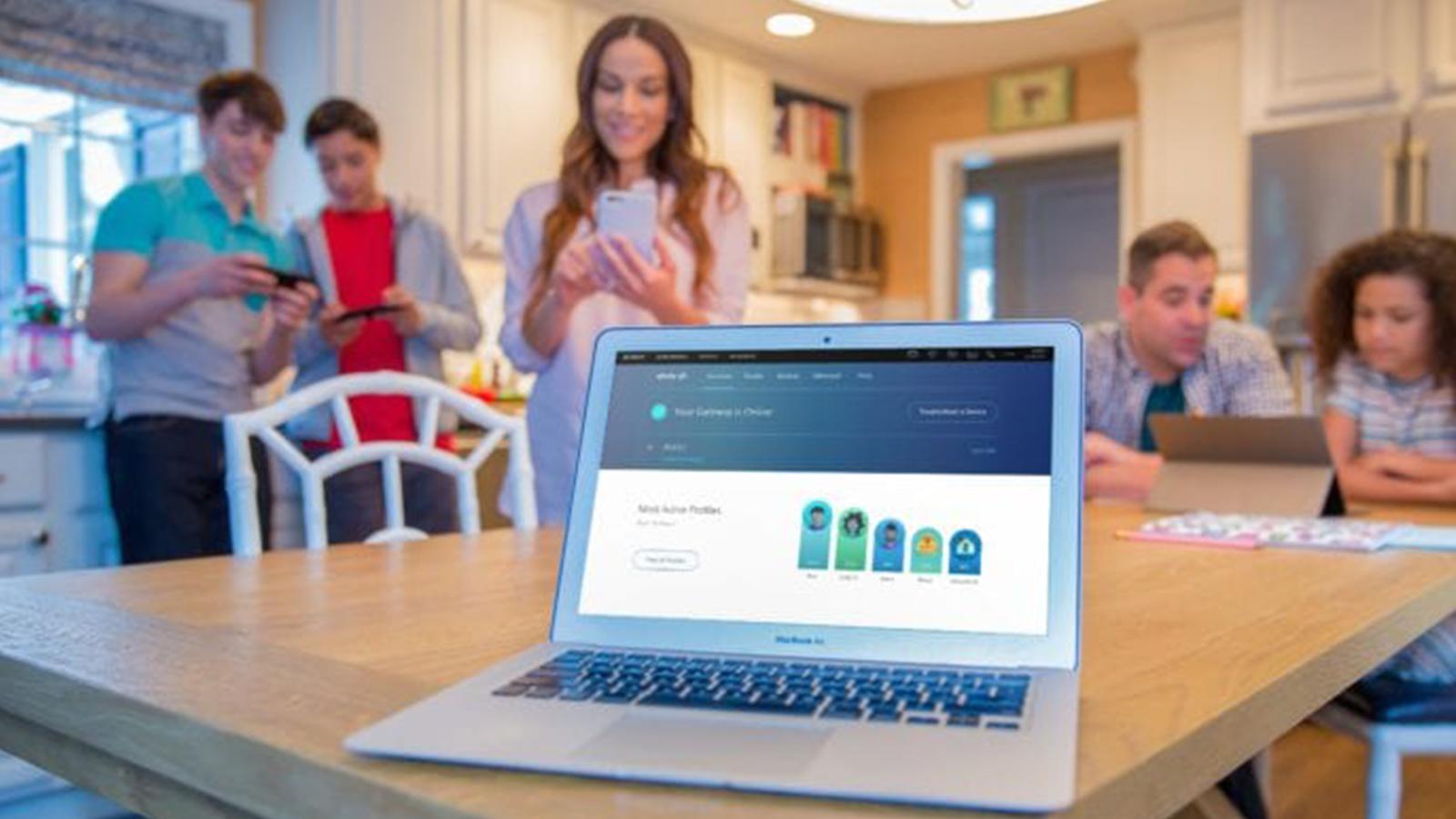 A laptop displays the Xfinity xFi app.